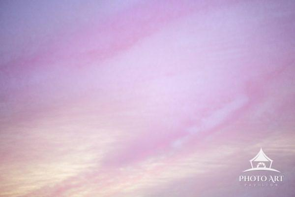 Beautiful wispy pink clouds against blue and purple sky at sunrise in Pennsylvania.