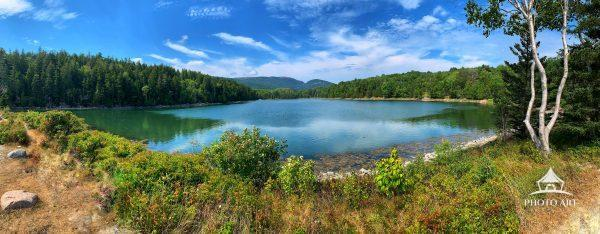A panoramic view of a peaceful lake with no one else around. This is in Acadia National Park in Bar